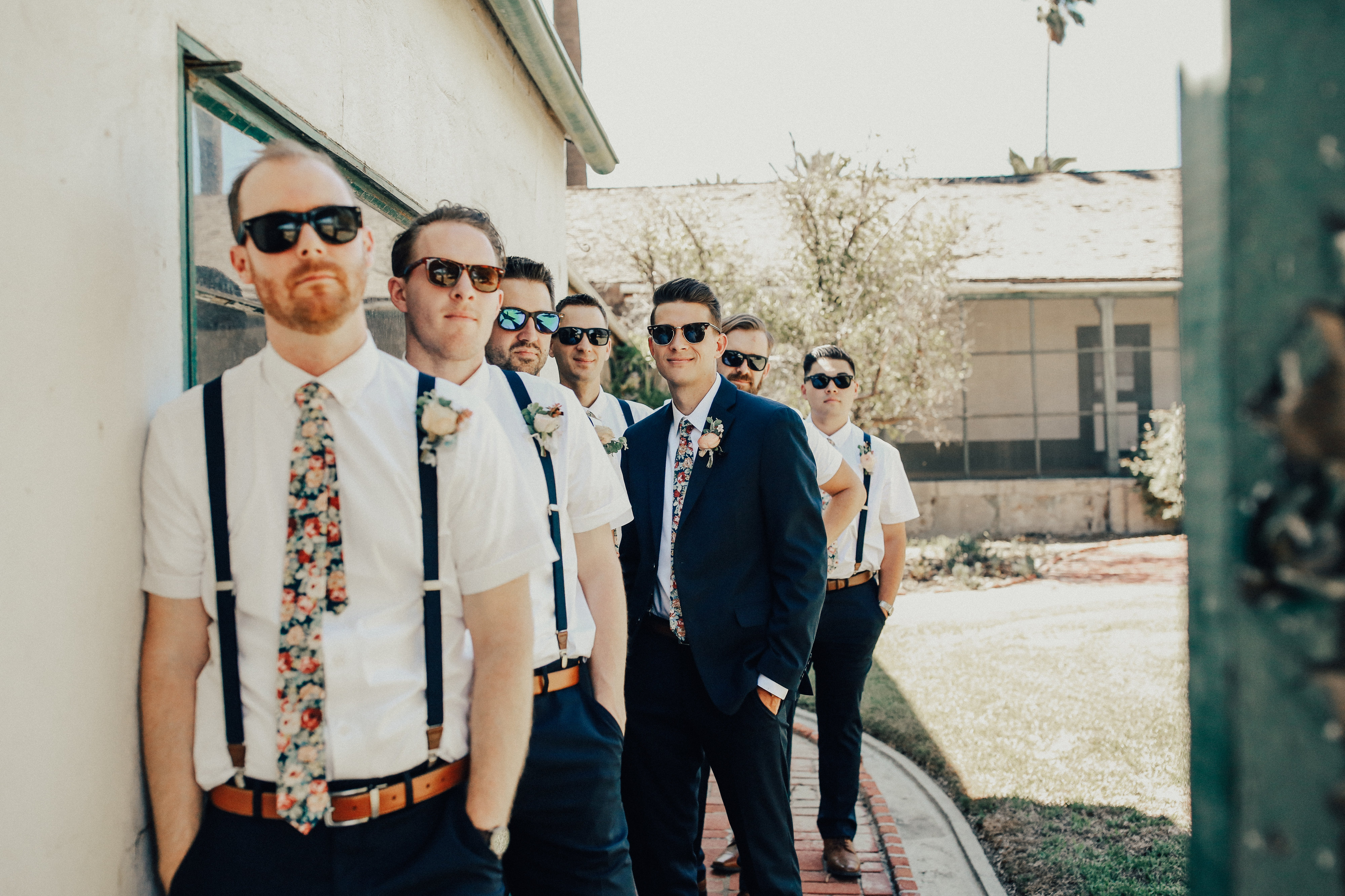 Groomsmen in blue suits and suspenders wear sunglasses and pose on wedding day