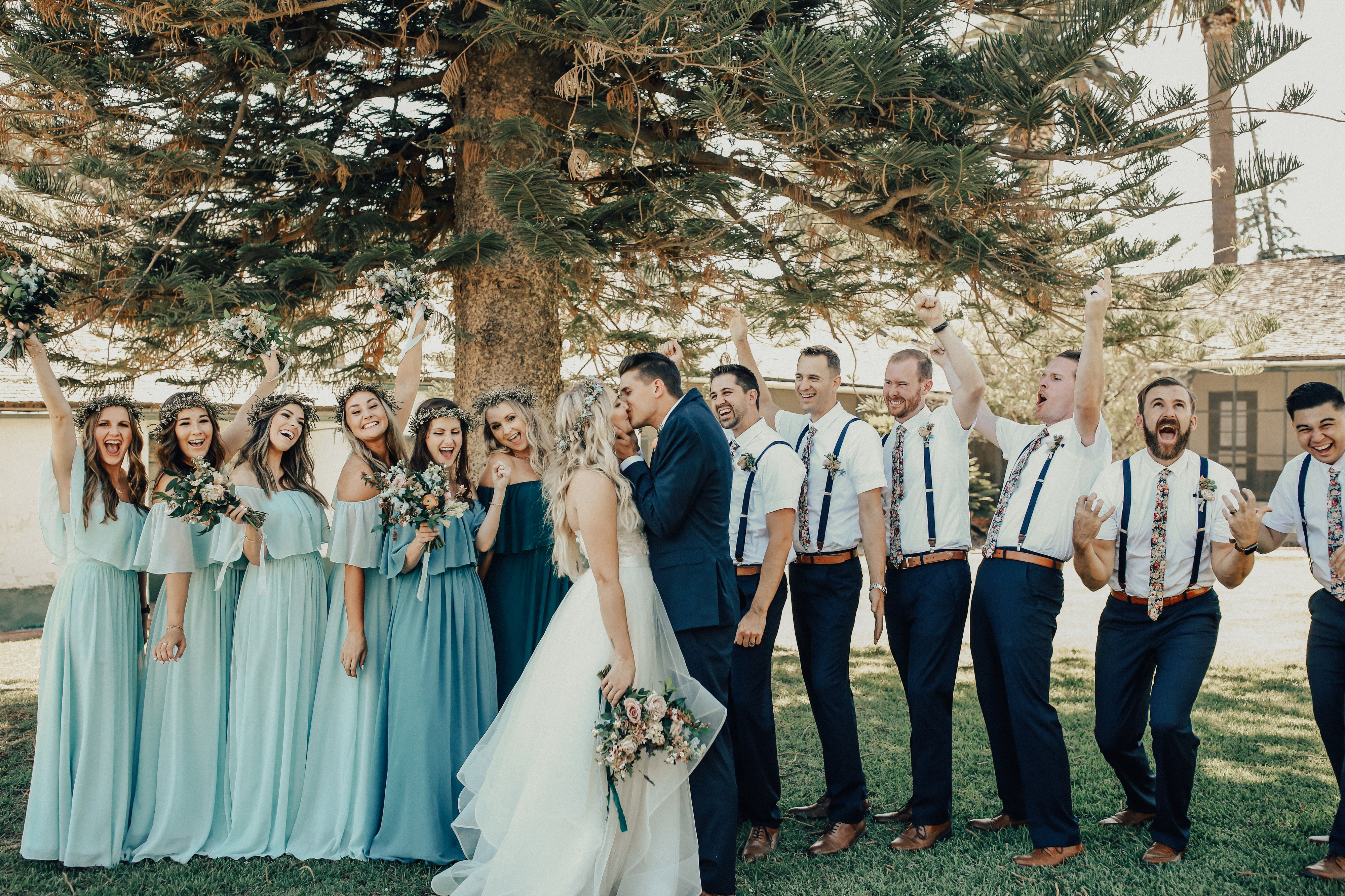 Bride and groom kiss at california wedding wedding party cheer and laugh with funny faces