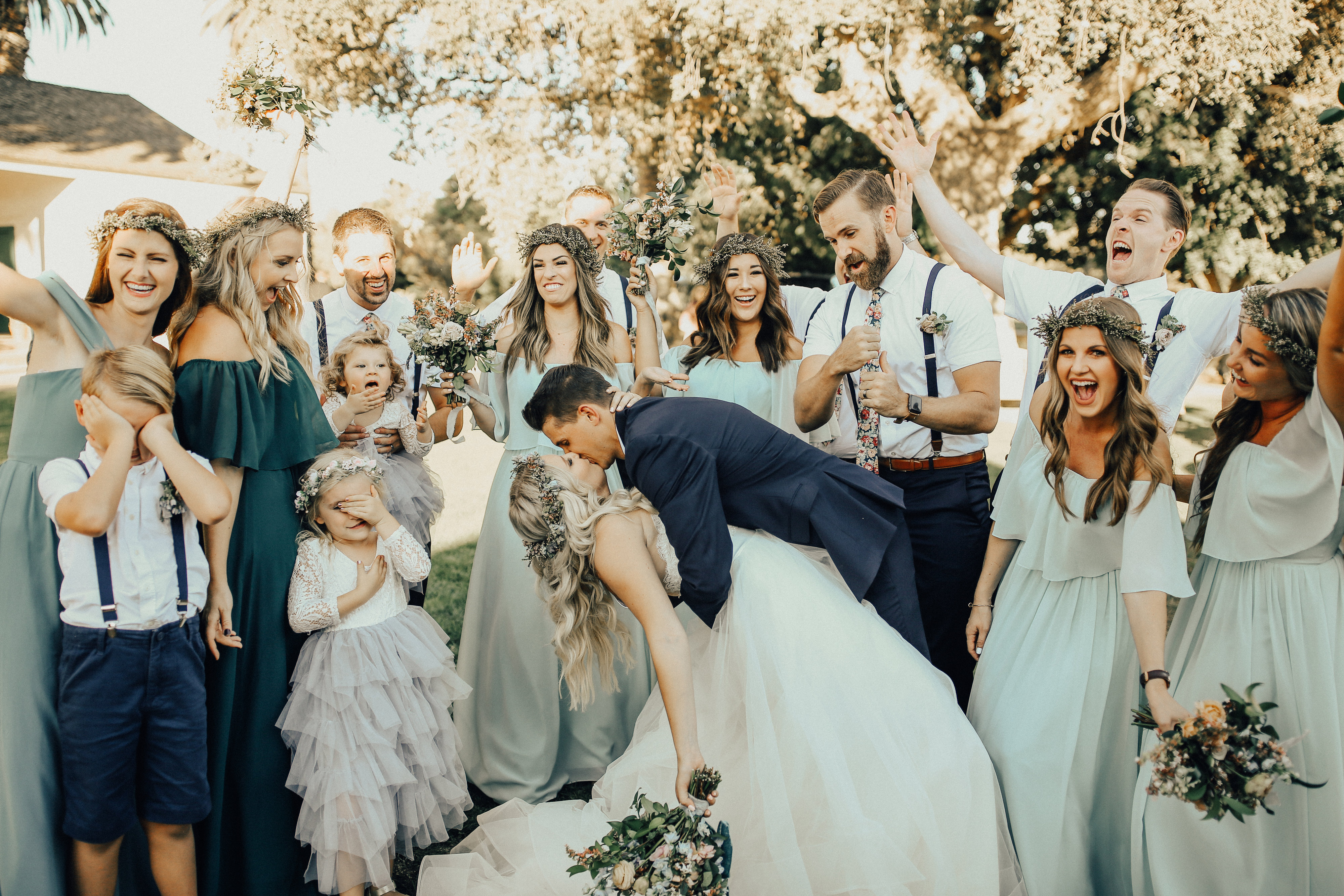 Bride and groom kiss after wedding ceremony as wedding party and guests cheer and flower girl covers her eyes