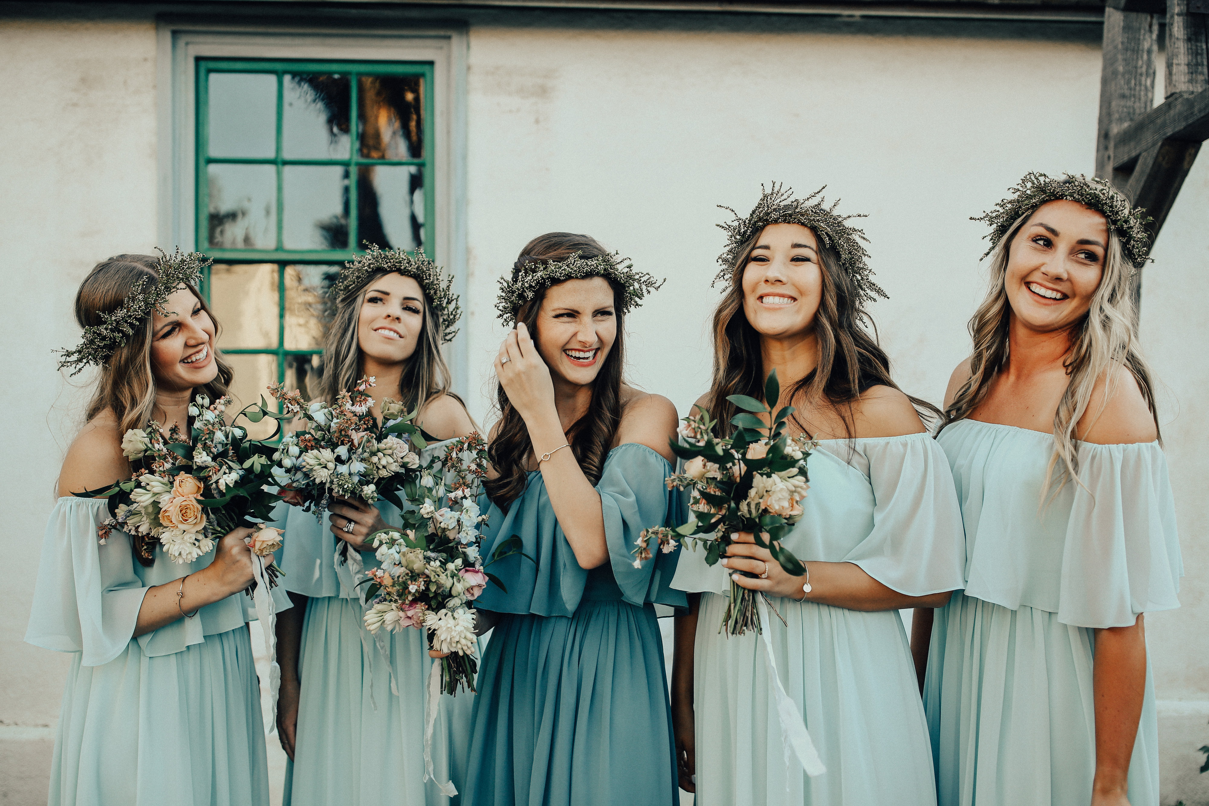 Bridesmaids in Revelry chiffon dresses in different blue and green hues wearing flower crowns