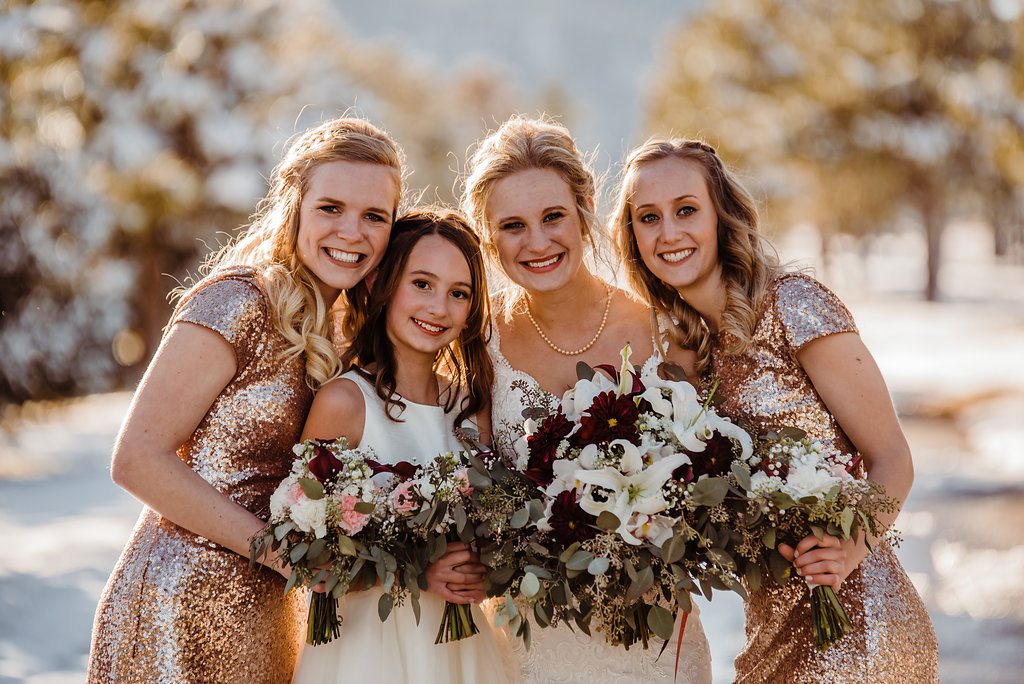 Rose Gold sequin bridesmaids smile with bride in the snow.