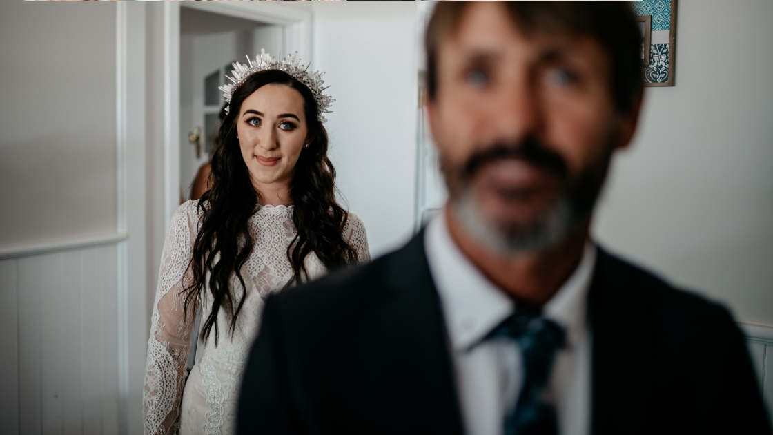 Bride in high neck lace wedding dress dark hair with jewel crown smiling and looking at dad on wedding day first look with father