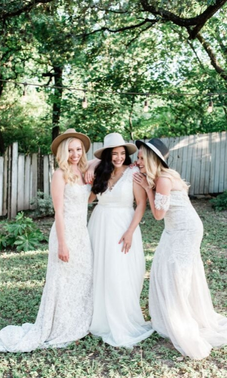 Three brides in revelry bridal gowns wearing hats smilinf and posing in yard of austin bar lenoir