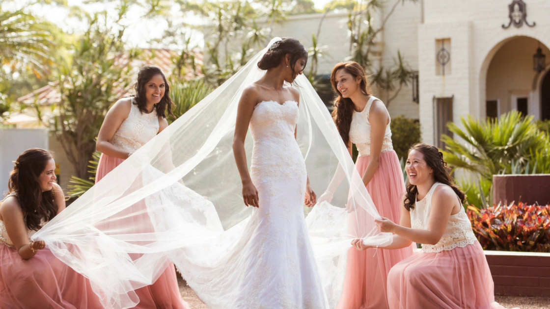 Bride surrounded by bridesmaids in tulle skirts and lace tops holding different corners of her vail and creating a stunning effect for bridal party portraits.