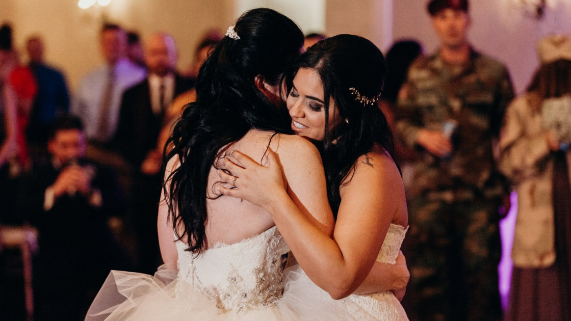 Two brunette brides dark haired wives hugging and dancing first dance in wedding day at wedding reception