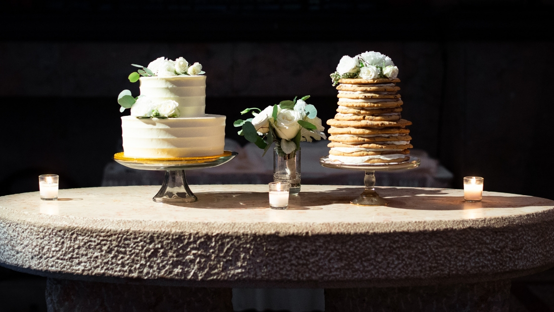 Wedding cake two tier white textured with flowers and greenery chocolate chip cookie cake icing tea lights florals
