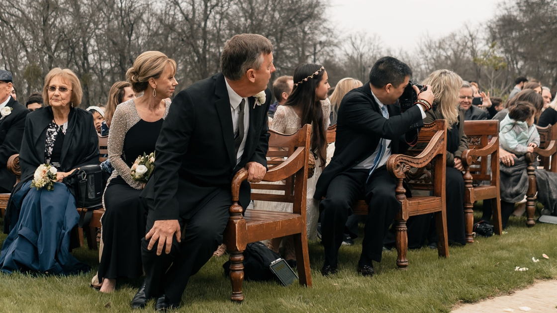 Wedding guests in brown pews outside turn and wait for beautiful bride in revelry wedding dress to walk down aisle