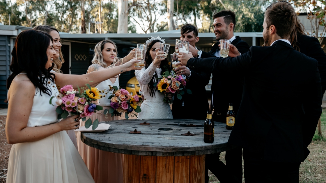 Wedding party cheersing after ceremony celebrating marriage at round wood table